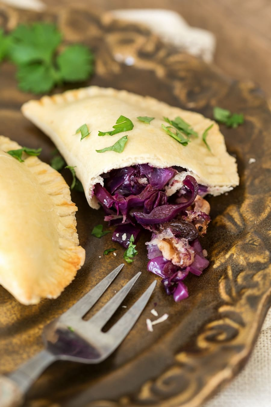 Veggie empanadas showing the filling made with red cabbage, onion, raisins and walnuts.