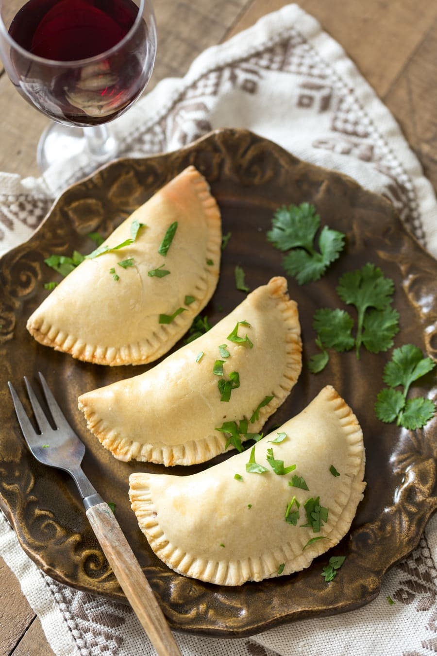 Veggie empanadas on a brown plate, decorated with cilantro.
