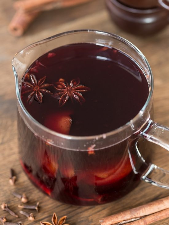 Glass jug with vin brulé. Star anise pods on the surface.