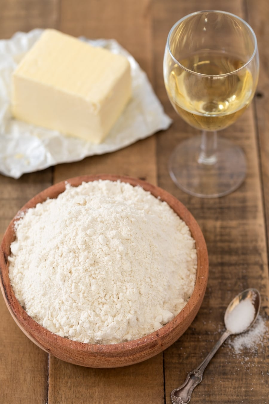 Bowl of flour, white wine glass and butter.