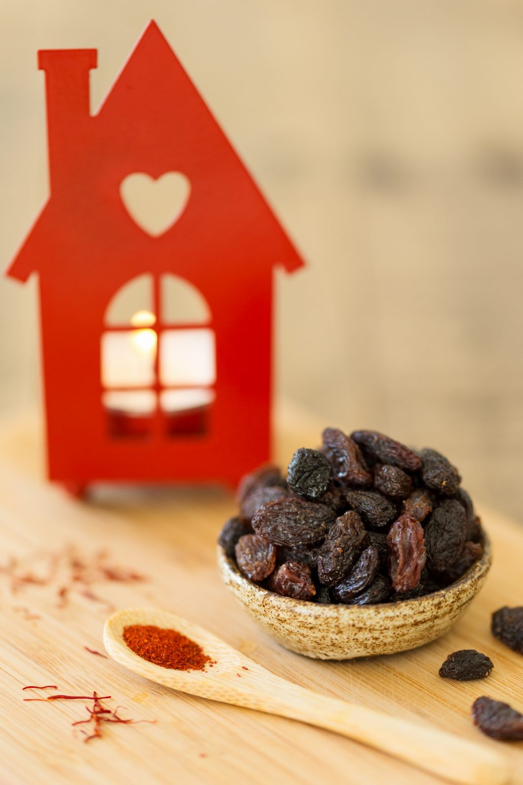 Bowl of raisins, saffron on a spoon, house-shaped candle holder.