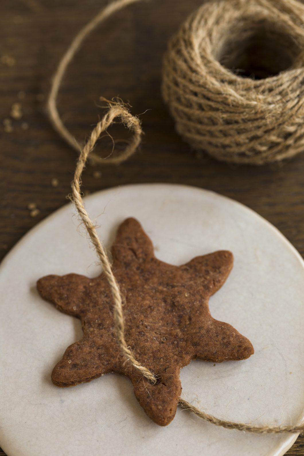 Jute twine being passed through a hole in a Swedish ginger thin cookie to use as Christmas tree ornament.