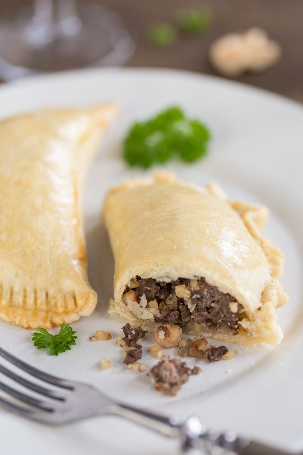 Homemade empanadas with venison and hazelnut filling, with filling coming out.