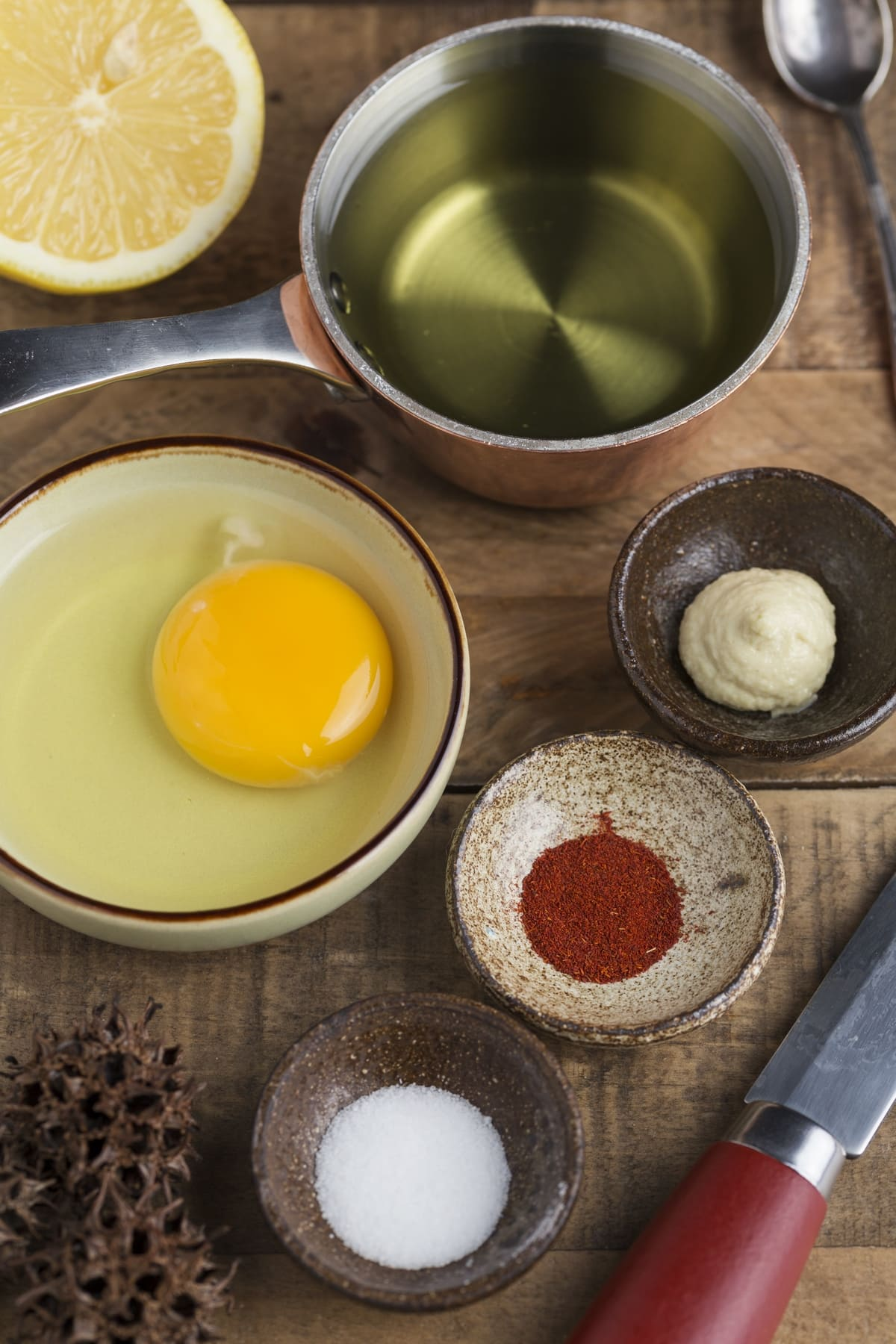 Small bowls containing spices, egg, oil and a half lemon.