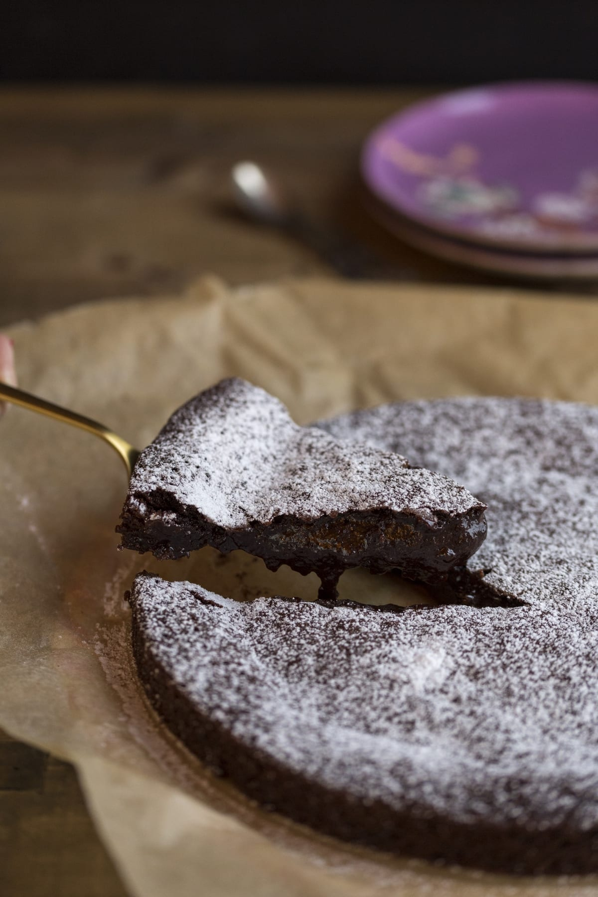 A slice of kladdkaka being lifted on a cake spatula.