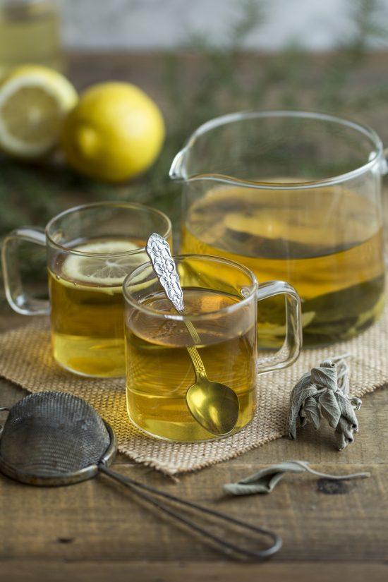 Lemon sage herbal tea in see-through jug and mugs.