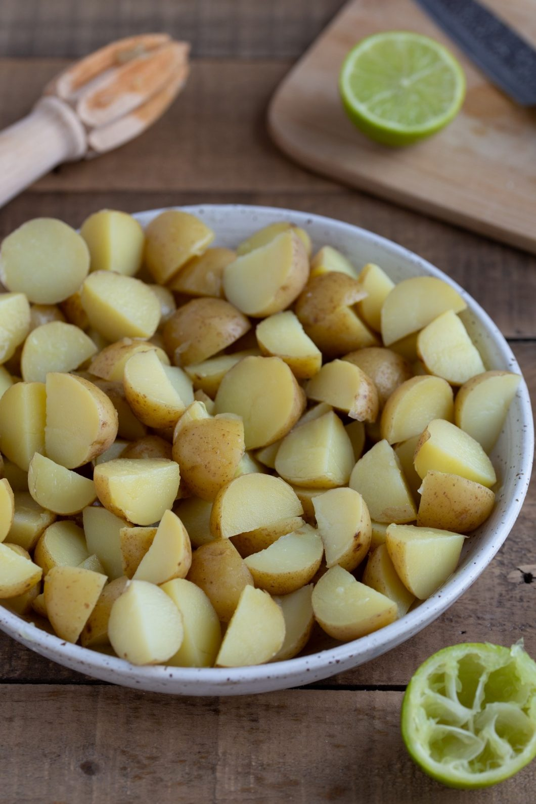 Baby potatoes, cooked, cut in quarters and placed in a bowl.