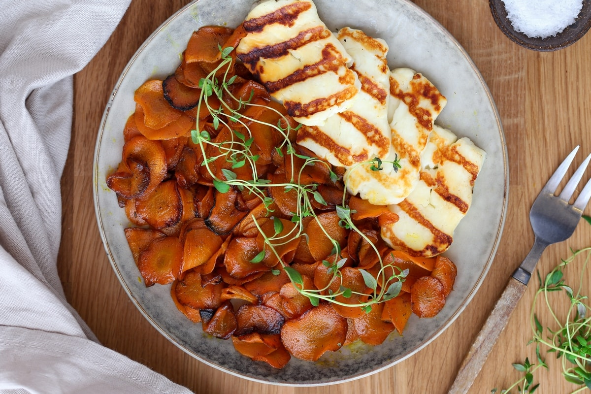 A portion of butter sauteed carrots with fresh thyme and grilled halloumi.