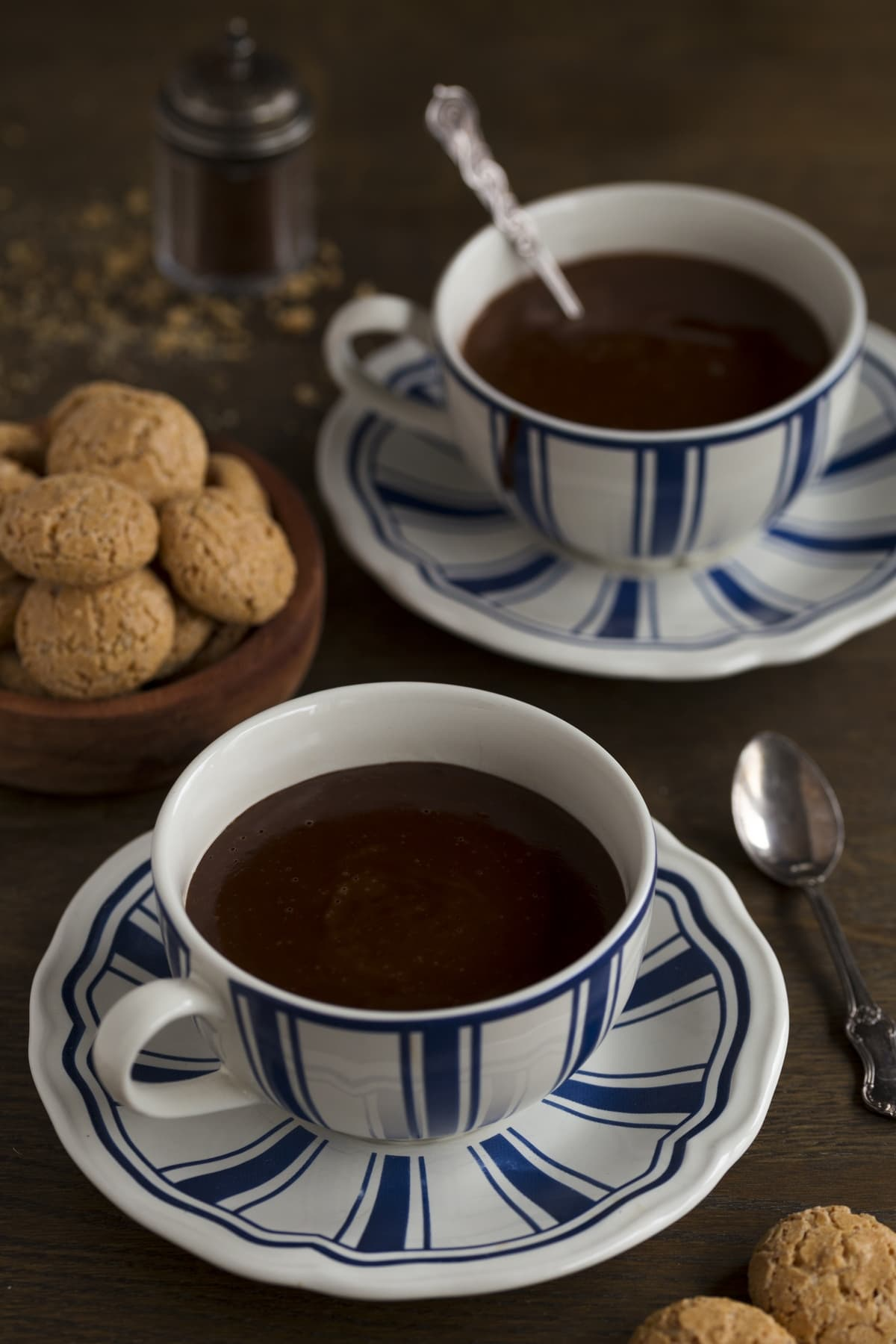 Two cups of hot chocolate on a dark table.