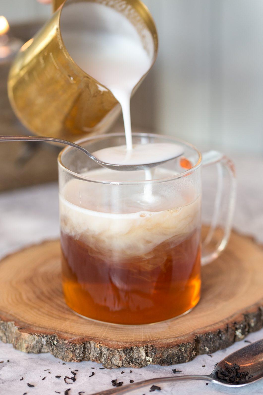 Adding steamed milk to tea.