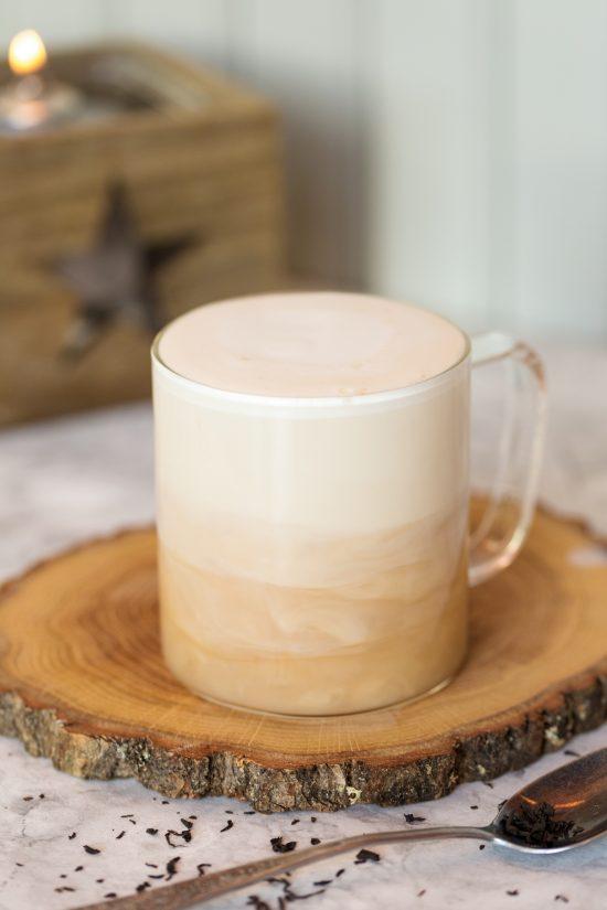 London fog tea latte in a glass mug showing the milk layering over the tea.