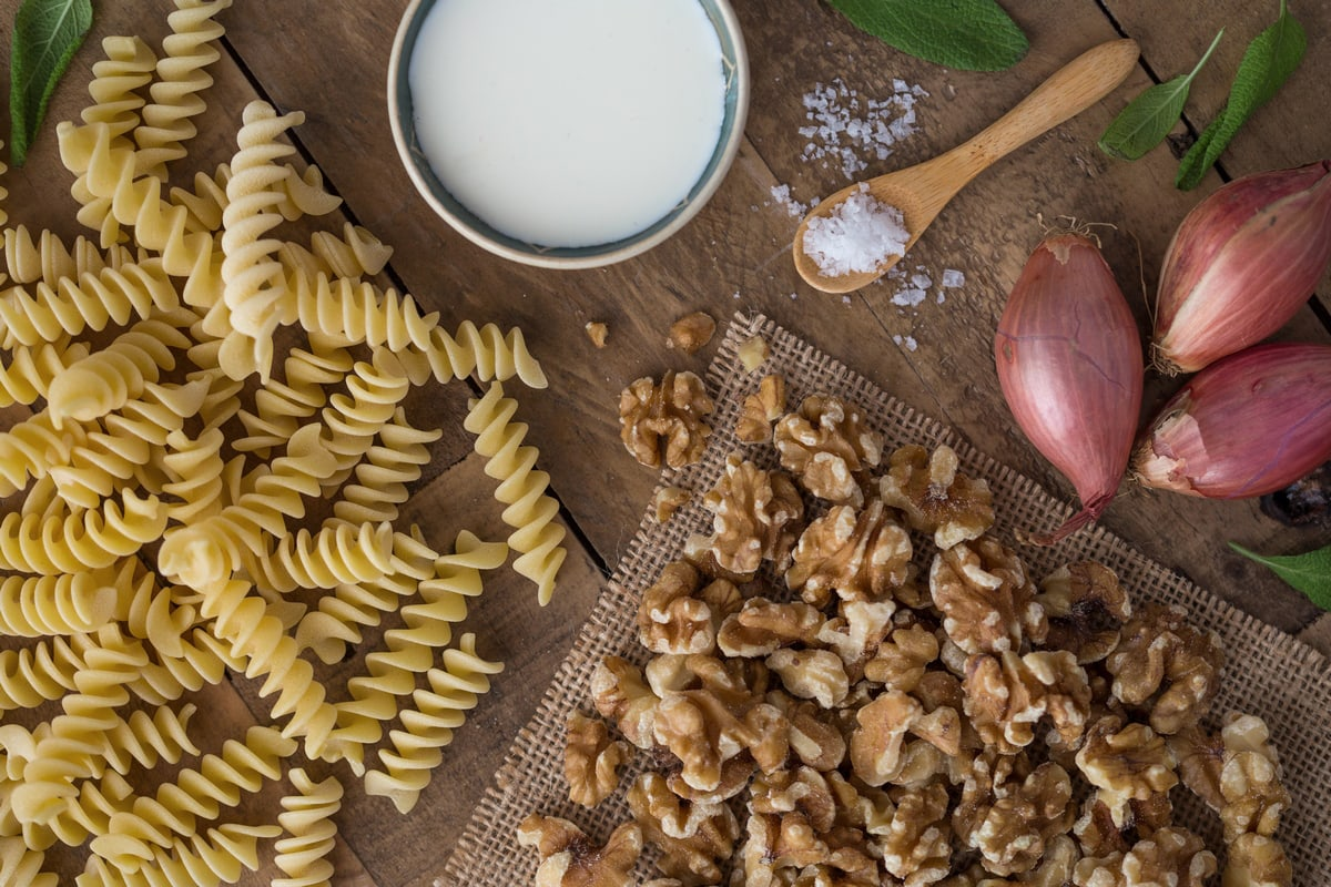 Pasta, walnuts, shallots, a spoonful of salt and a small bowl of cream on a wooden table.