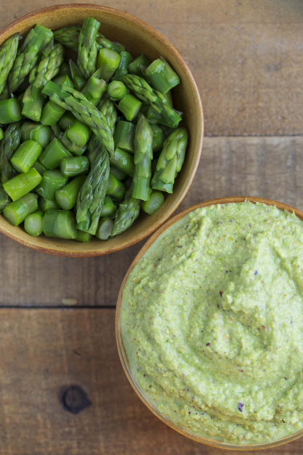 One bowl with puréed asparagus and one with chopped asparagus.