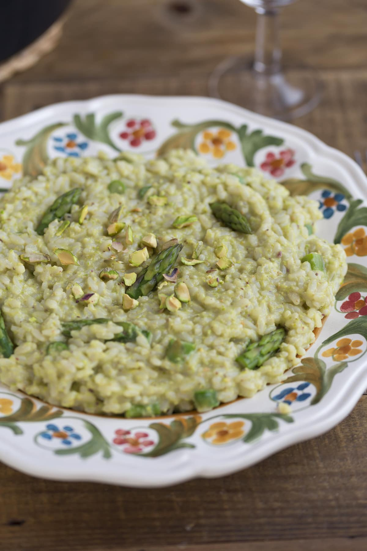 Pistachio asparagus risotto served on a decorated plate.