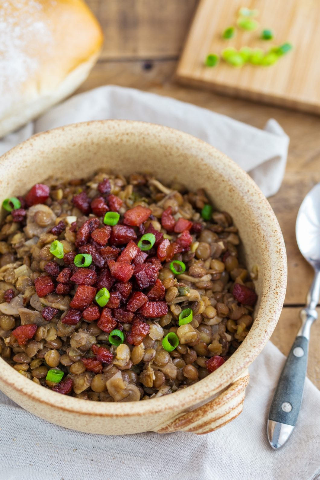 Crispy bacon and fresh spring onion topping a portion of lentil stew.