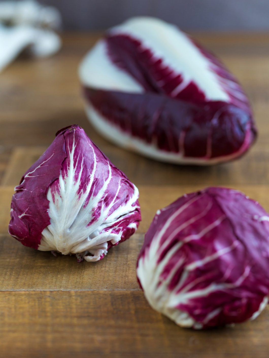 Small round radicchio heads and a long radicchio in the background.