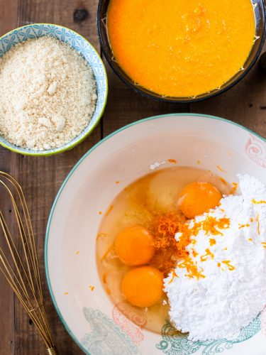 Eggs, sugar and orange zest combined in a bowl.
