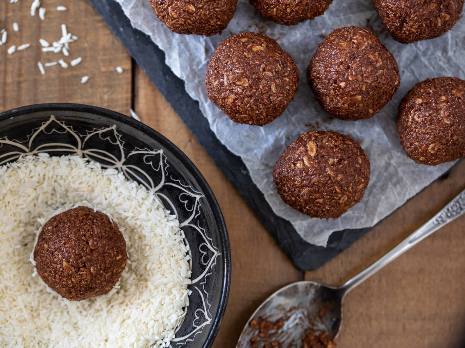 Chocolate oatmeal balls being tossed in shredded coconut.
