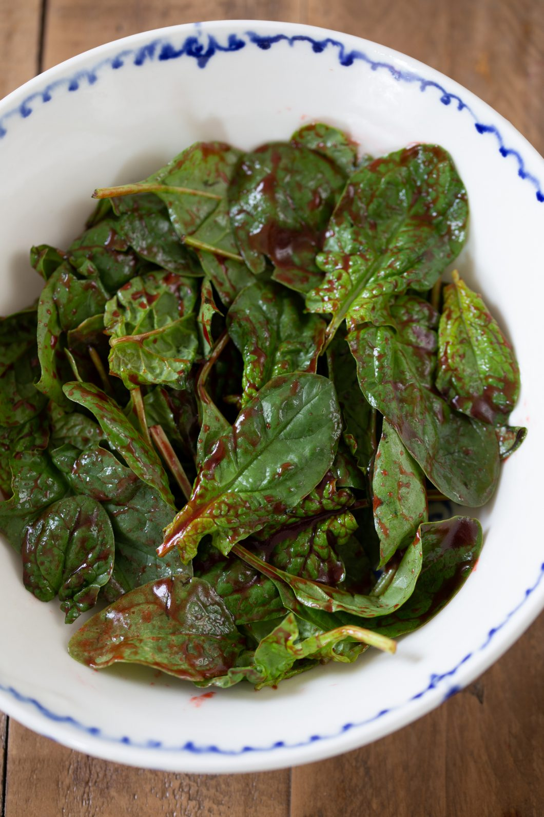 Tossing spinach leaves in dressing.