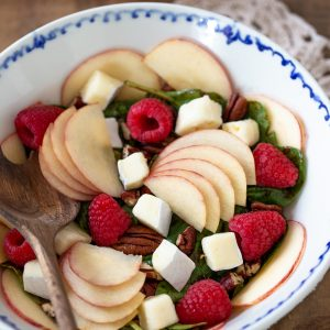 Apple brie and raspberry salad in a white bowl.
