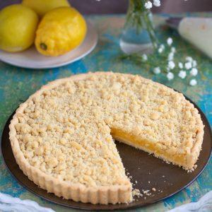 Ginger lemon pie on brown plate, one slice missing.