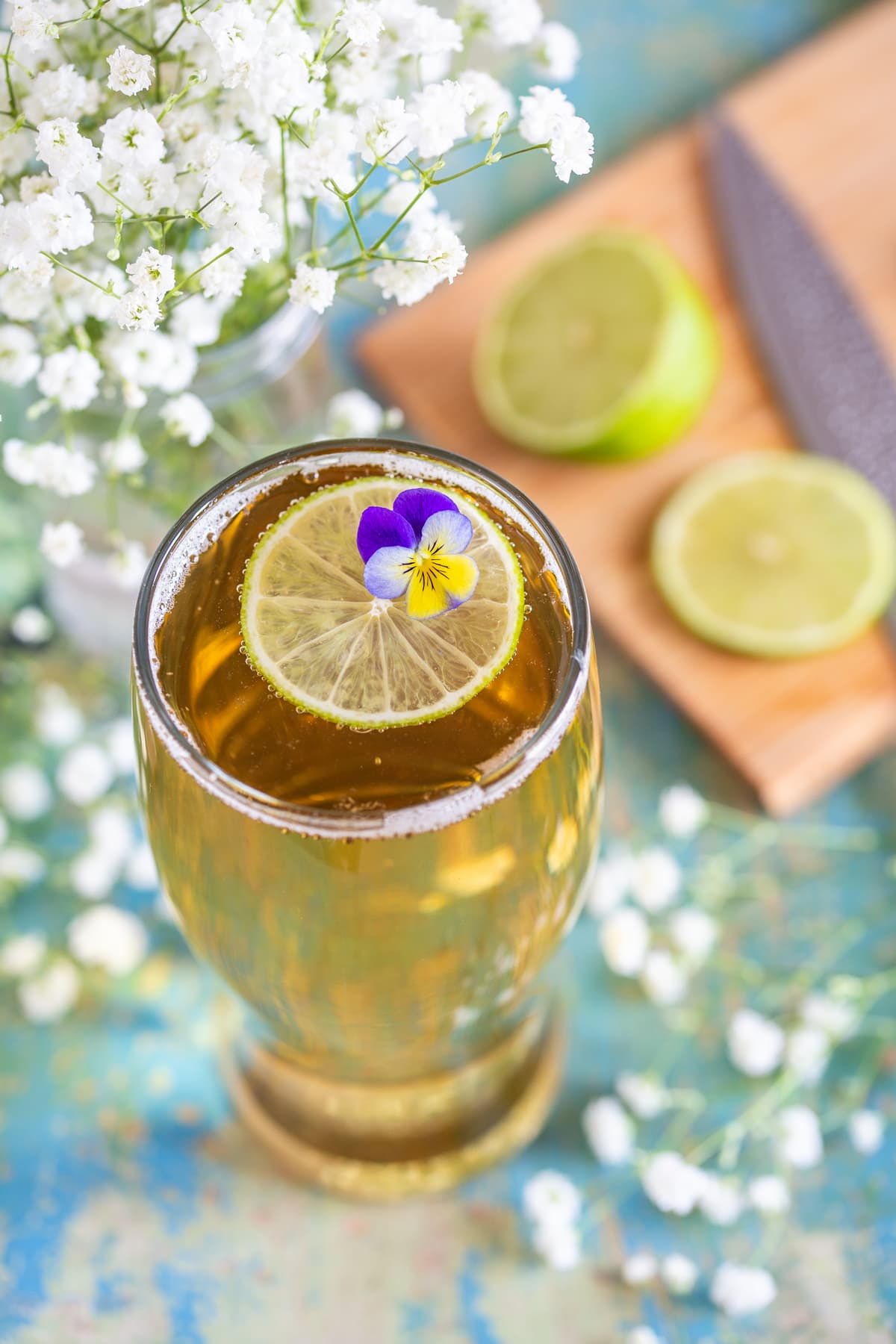 A little edible flower and lime slice decorating the top of the drink.
