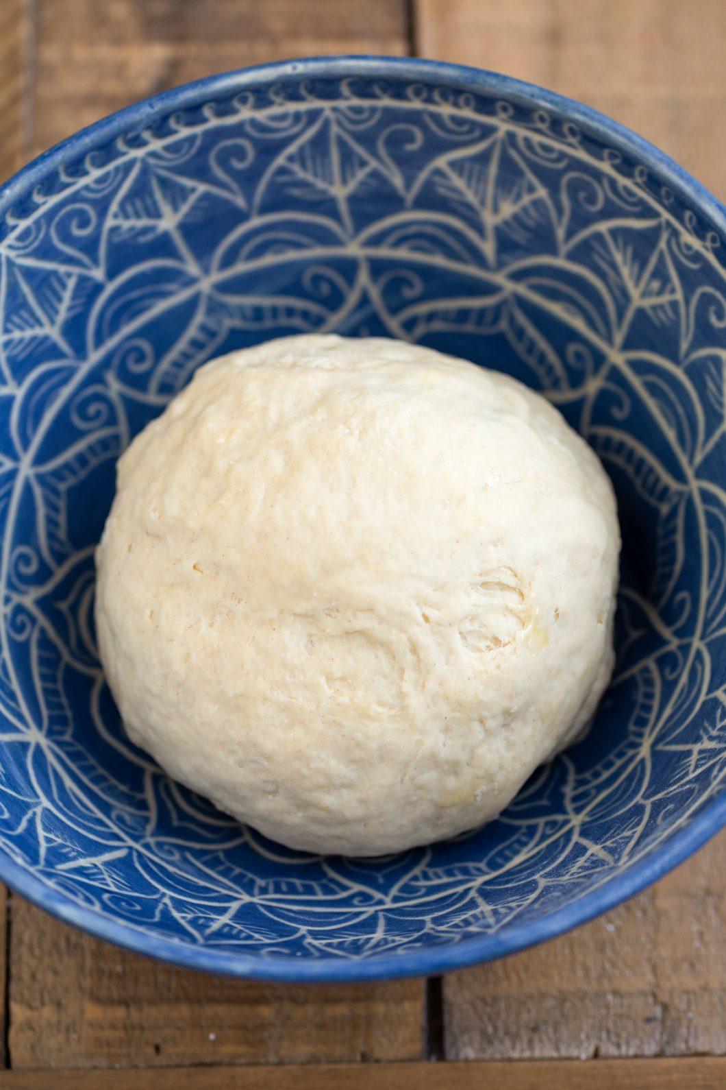 Pizza dough ball in a blue bowl.
