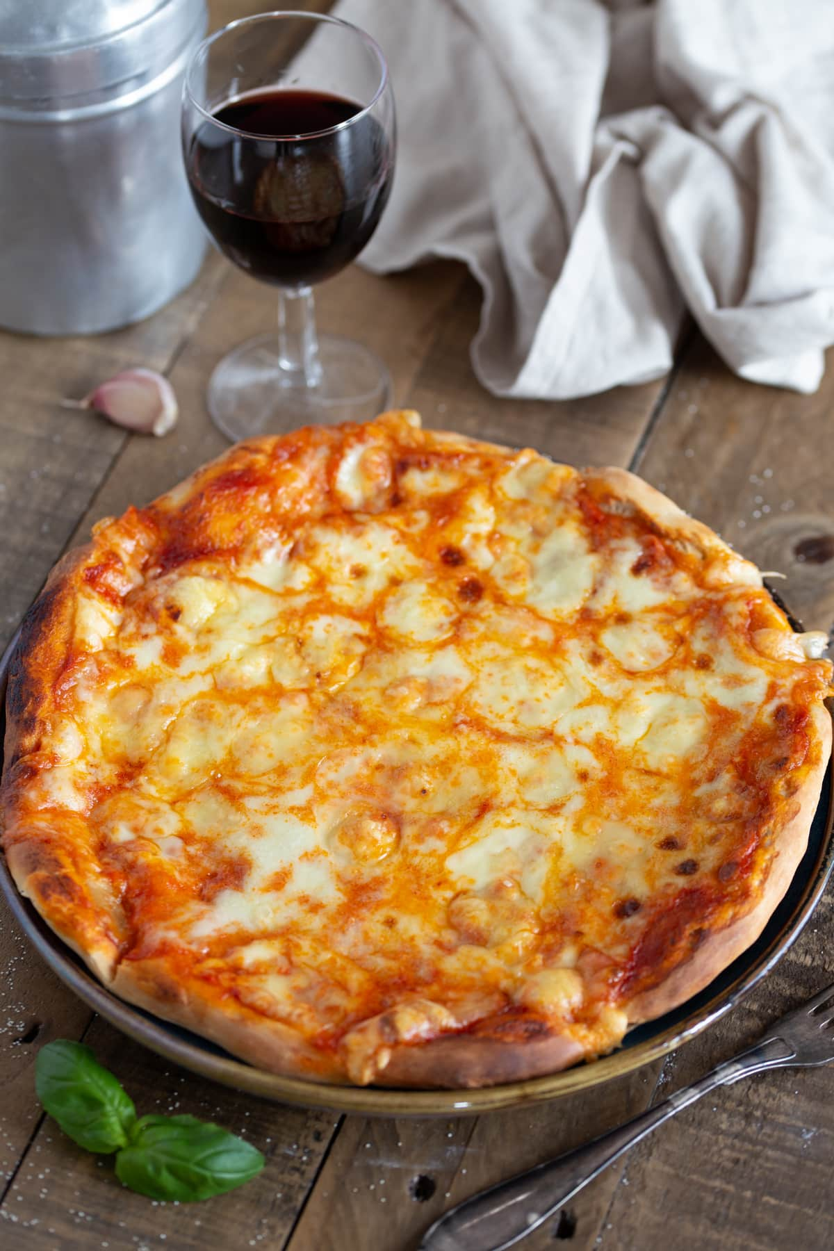 Cheese pizza served with a glass of red wine.