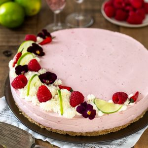 Raspberry chili cheesecake decorated with raspberries, lime, chilies and edible flowers.