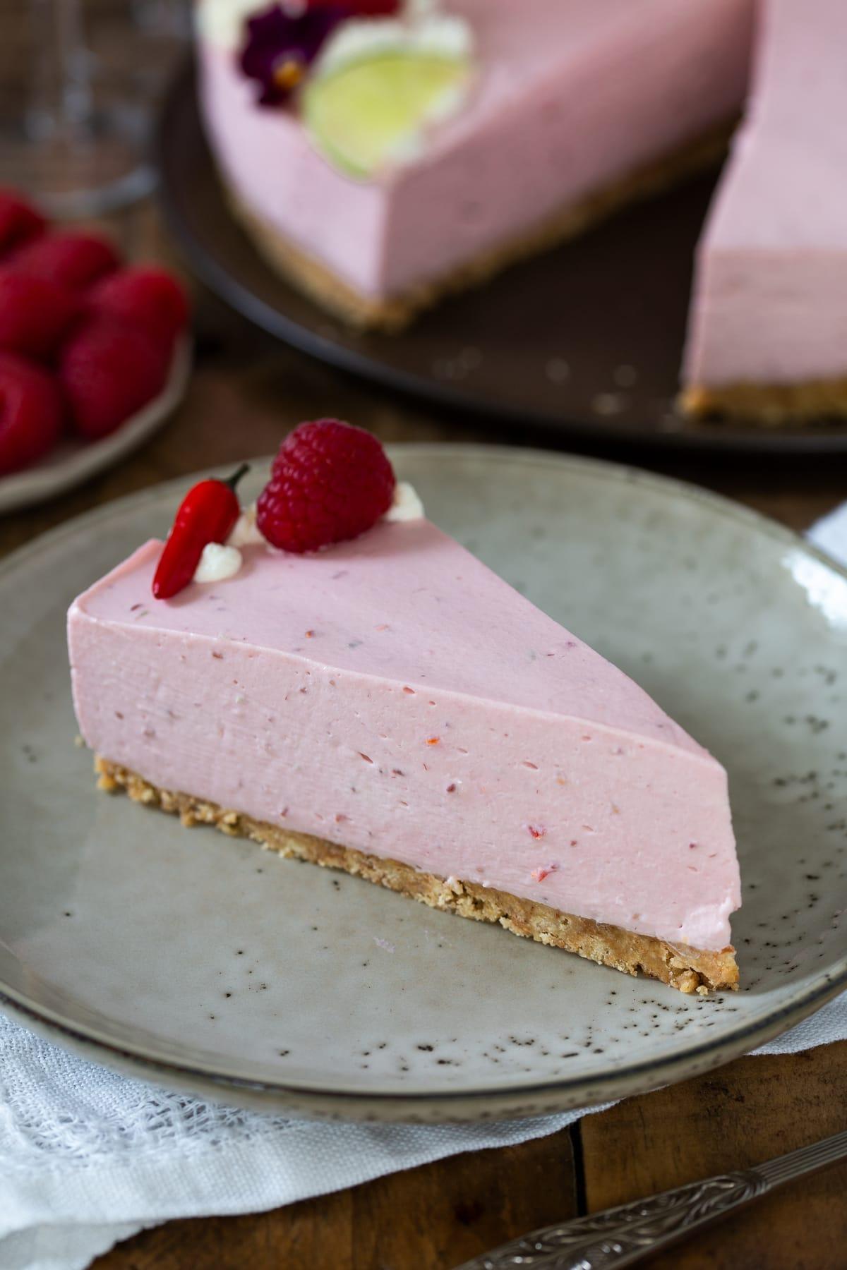 A slice of raspberry cheesecake on a beige plate.