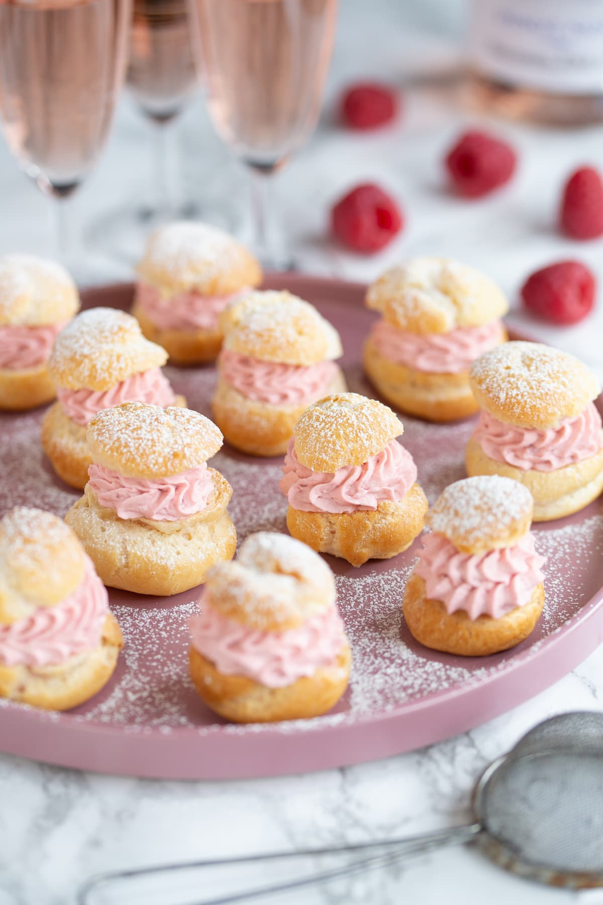 Homemade choux pastry puffs filled with raspberry cream.