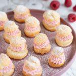 Raspberry cream puffs on a pink plate.