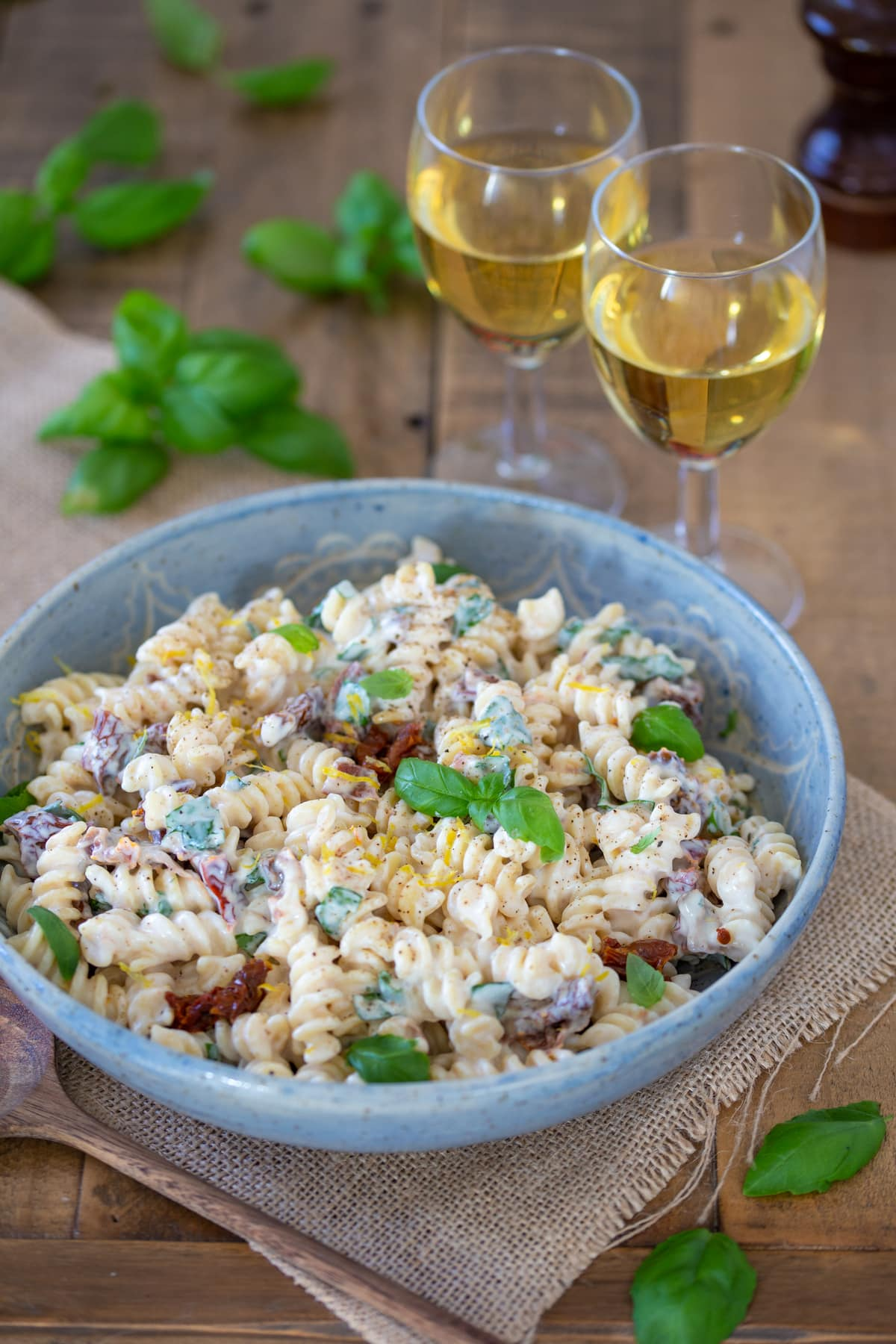 This pasta salad in a bowl, with 2 glasses of wine aside.