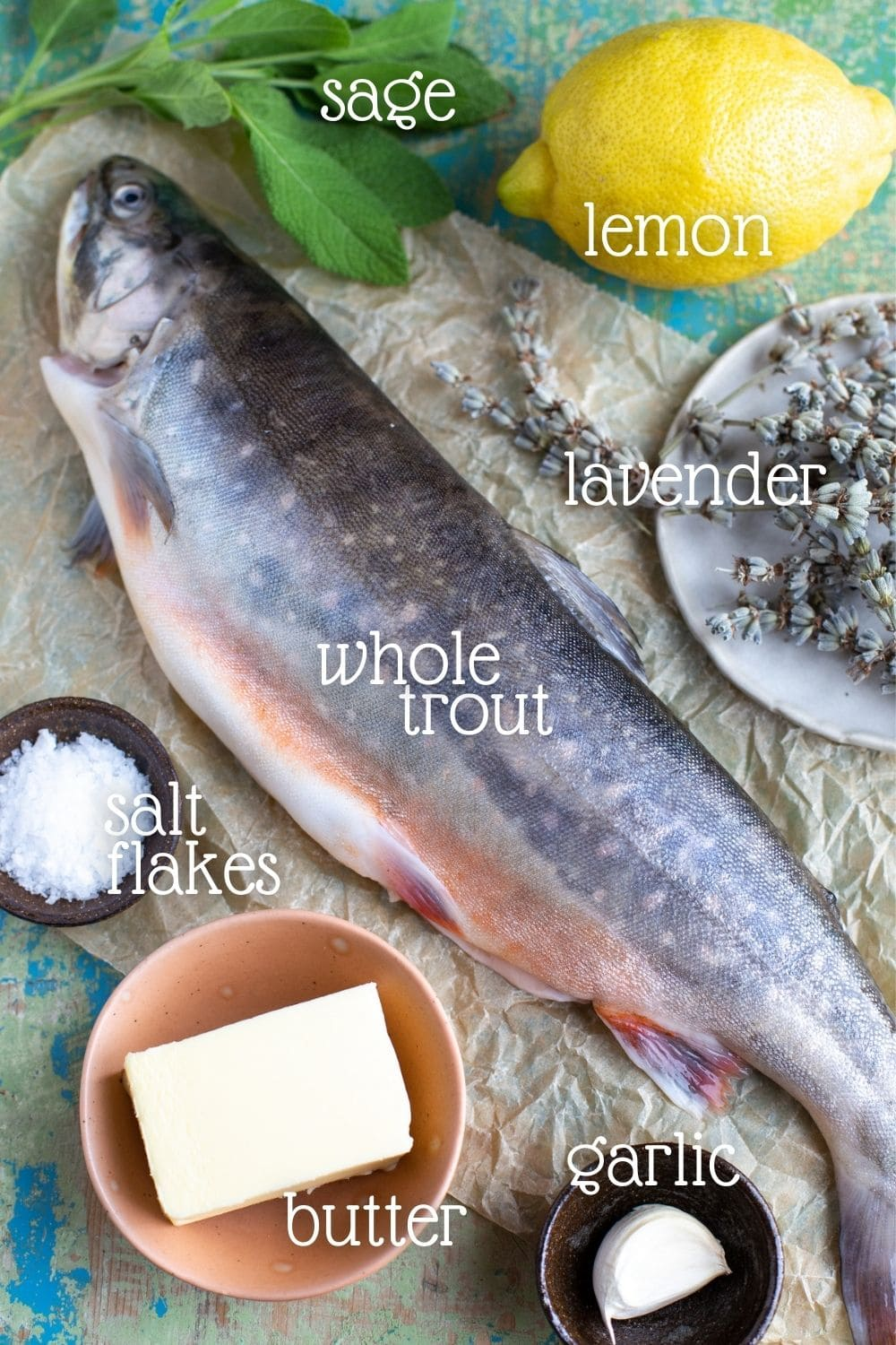 Whole trout surrpounded by the ingredients needed to prepare it.