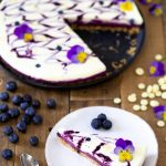 A slice of blueberry no-bake cheesecake with edible flowers.