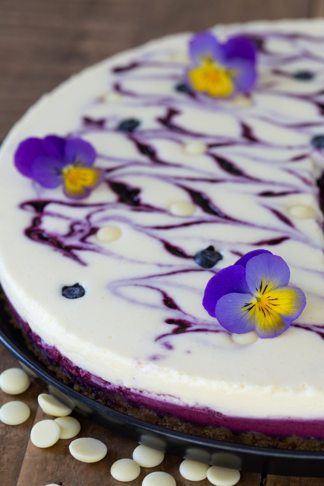 No-bake blueberry white chocolate cheesecake topped with pansies.
