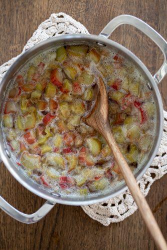 Cooking rhubarb in sugar water until soft.