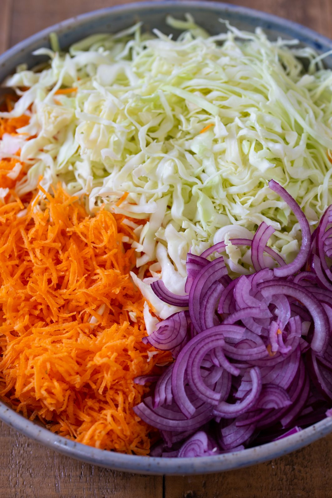 Thinly sliced carrot, white cabbage and onion together in a bowl.