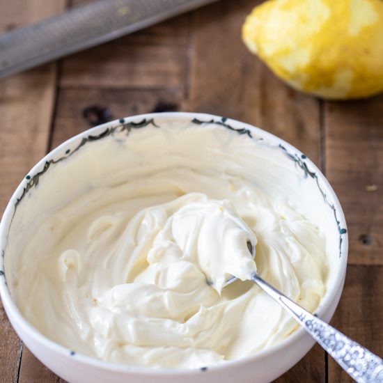 Cream cheese frosting i na bowl with a spoon inside, lemon and zester in the background.