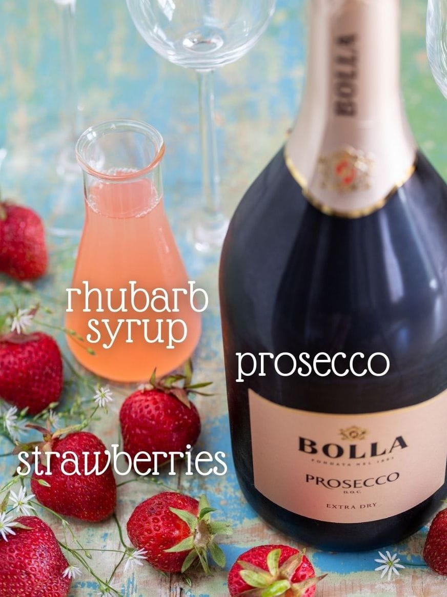 Fresh strawberries, syrup and a bottle of bubbels.