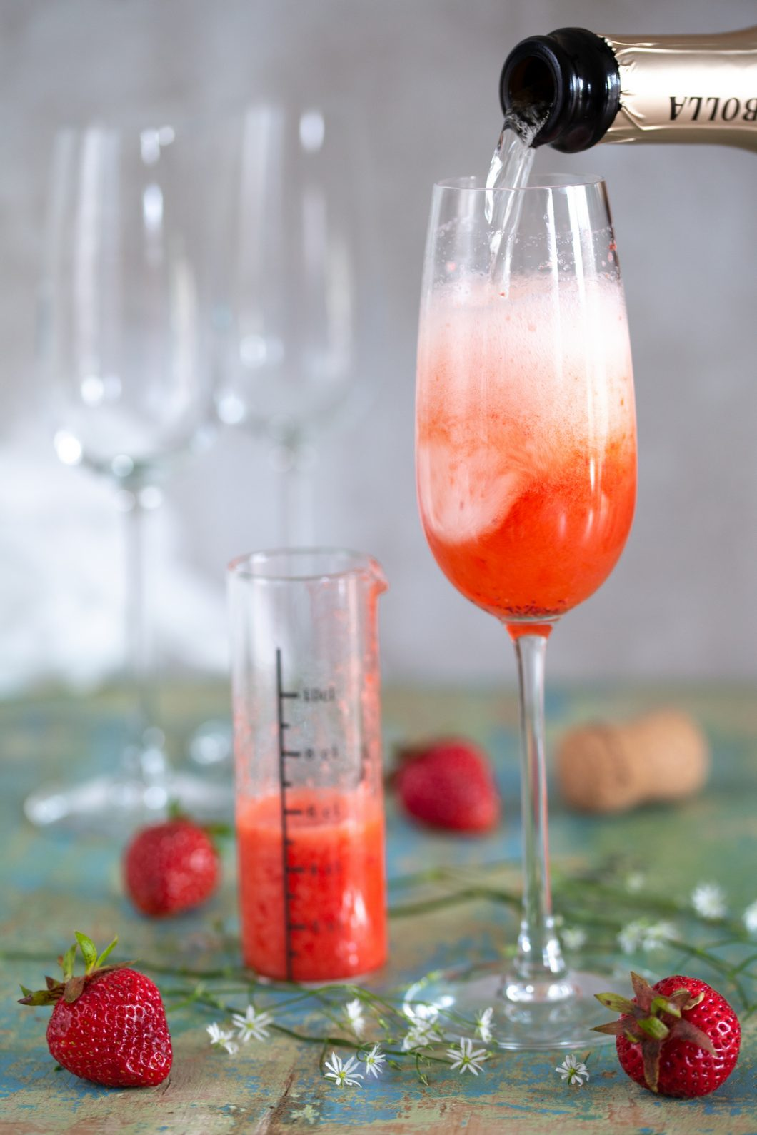 Prosecco and strawberry purée blending together.