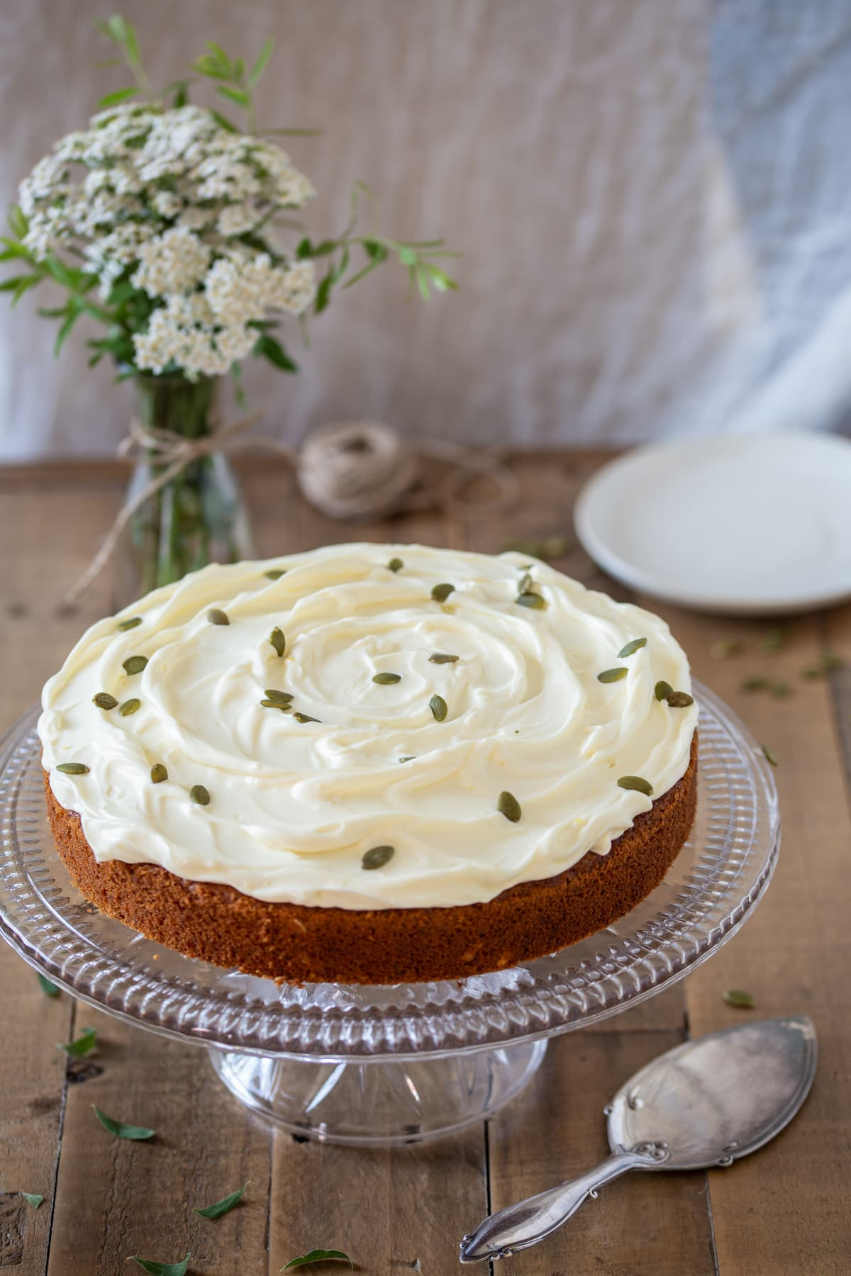 Carrot cake with pumpkin seeds over the frosting.
