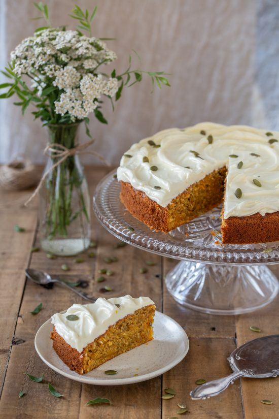 A slice of carrot cake on a plate, the rest of the cake on a cake stand.