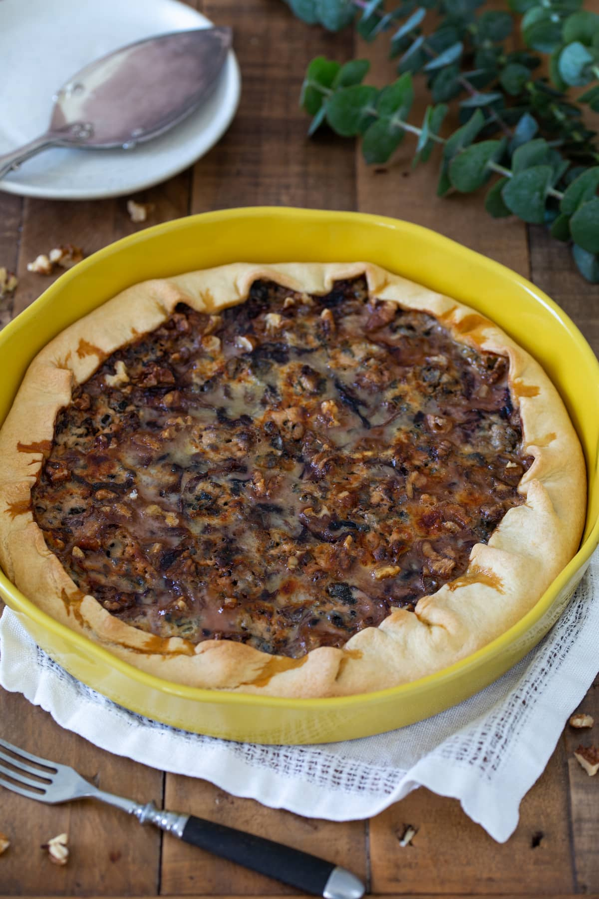 Radicchio and blue cheese quiche in a yellow ceramic pan.