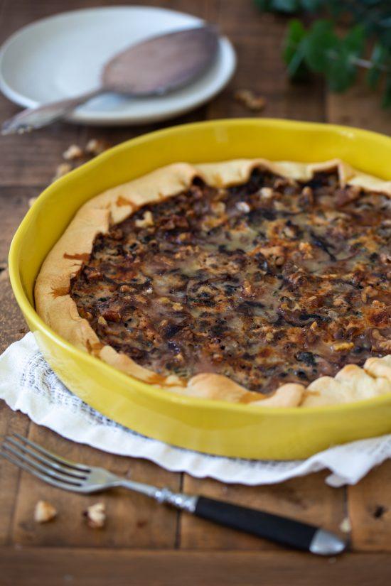Radicchio quiche with walnuts in a ceramic tart pan.