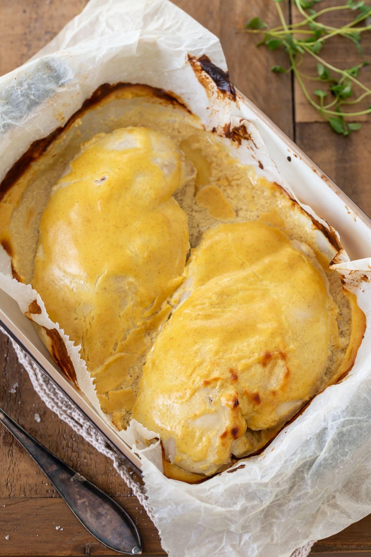 Baked mustard chicken in a casserole dish.