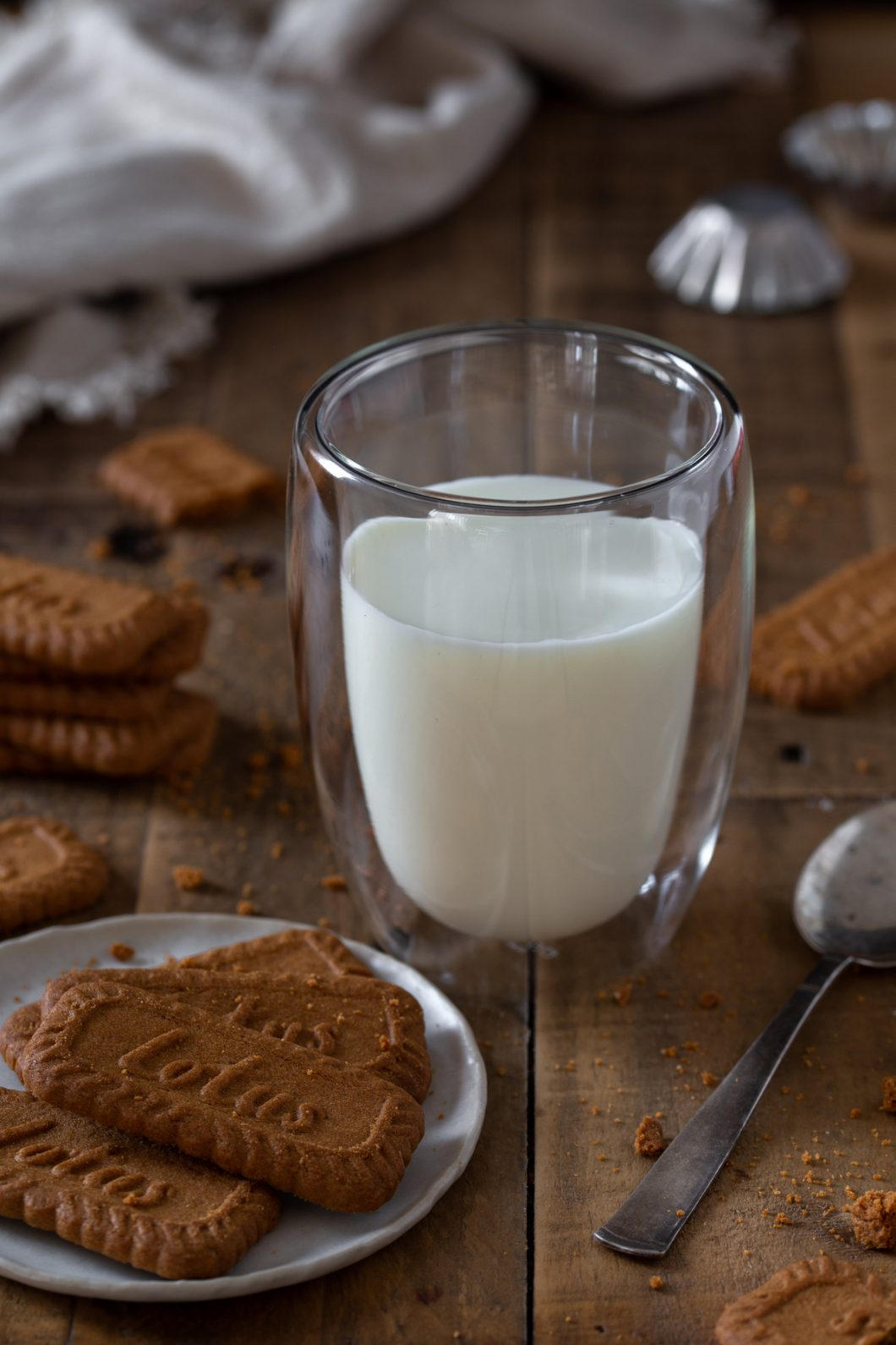 A glass of milk with biscuits all around.