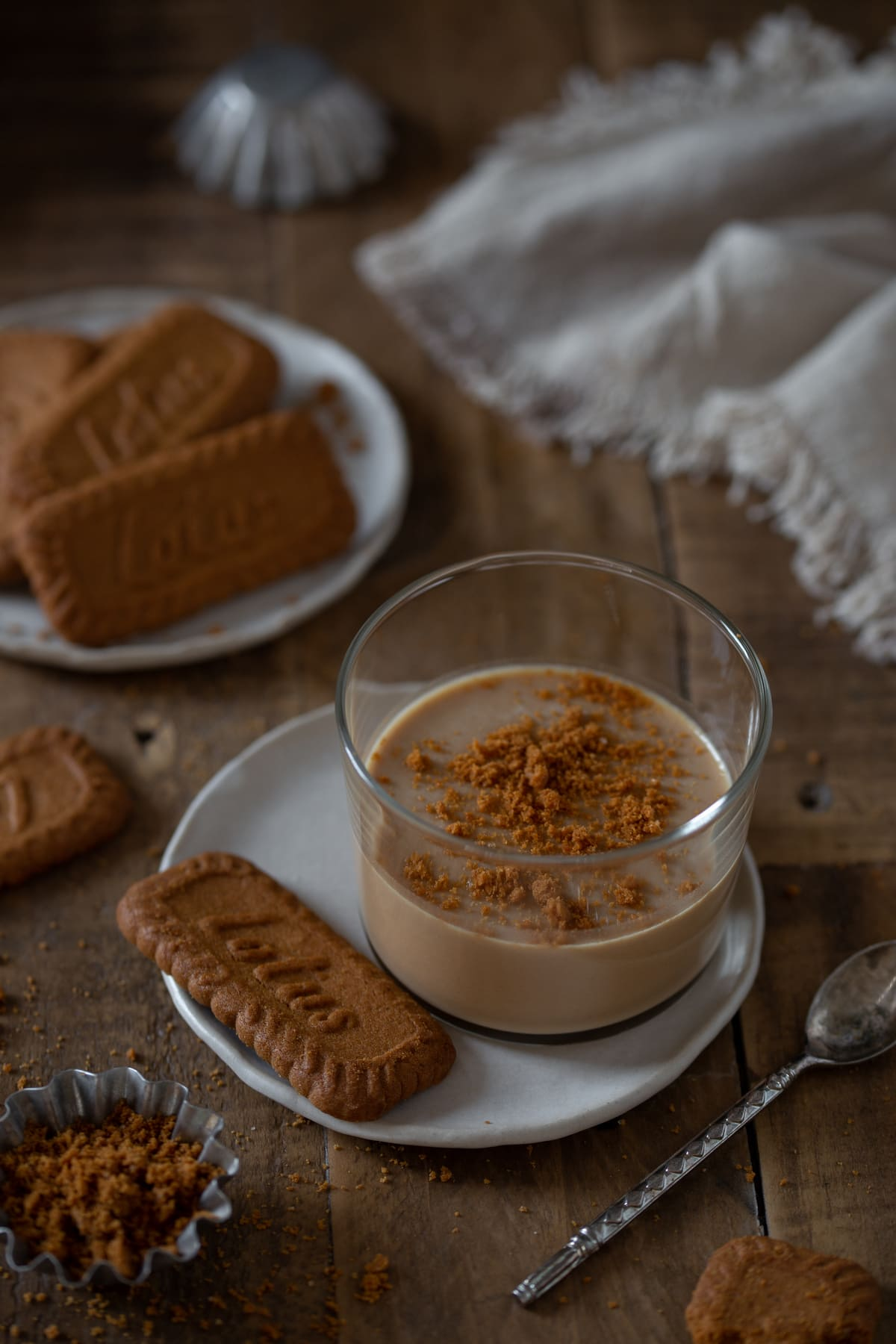 A single portion of Biscoff panna cotta served with a Lotus Biscoff biscuit on the side.