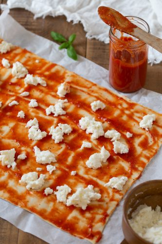 Puff pastry sheet topped with tomato sauce and grated mozzarella.
