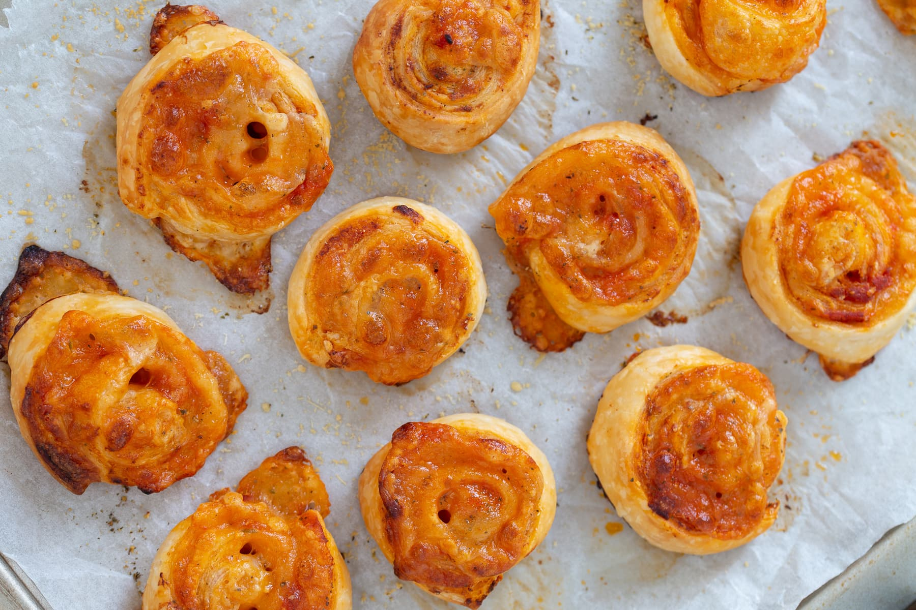 Pizza flavoured puff pastry pinwheels on baking paper.